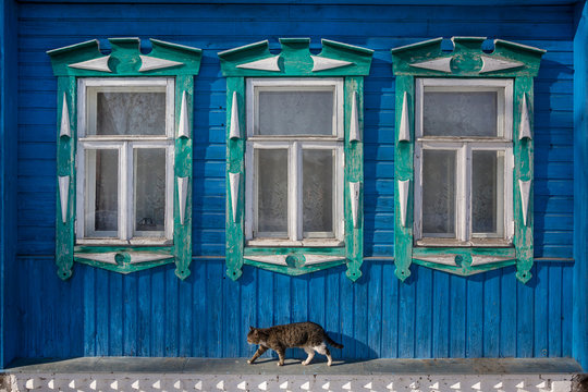 Windows with carved platbands on the blue old wooden house