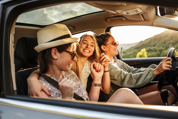 Group of best female friends travel together.They drives a car and making fun.Summer adventure.