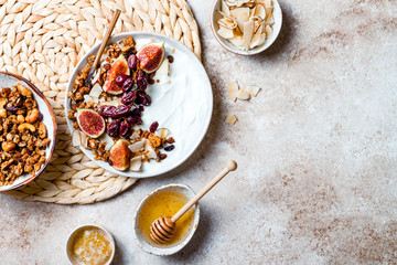 Breakfast bowls with granola, figs, roasted red grapes, yogurt, coconut chips and honey. Healthy vegan, vegetarian breakfast table