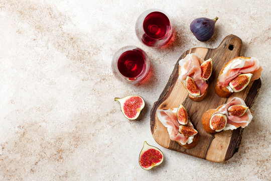 Crostini with prosciutto, cream cheese and figs on wooden board. Appetizers, antipasti snacks and red wine in glasses. Authentic traditional spanish tapas set. Light beige background. Top view