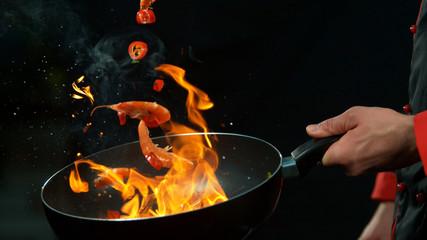 Closeup of chef holding wok pan with falling prawn