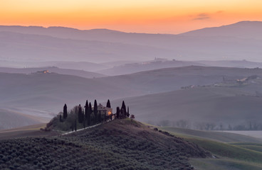 The Tuscan countryside in the province of Siena shrouded in morning mist before the dawn of a new day