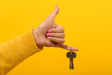 female hand holding house keys and showing thumb up, over yellow background