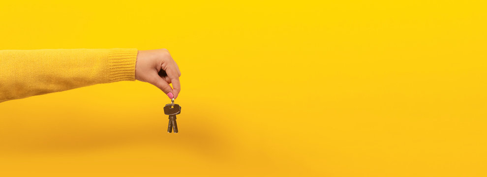 female hand holding house keys, suggesting, over yellow background, panoramic image.