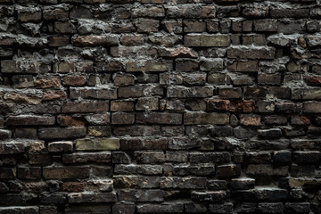 Urban black brick wall texture old masonry background. Gloomy background, black brick wall of dark stone texture