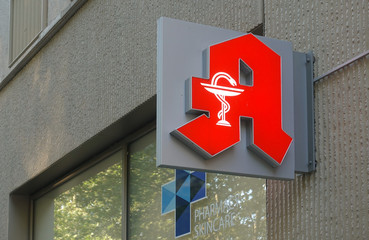 Sign with the red logo of the Deutsche Apotheke (German Pharmacy) mounted on a wall. Photo taken in Dresden, Saxony / Germany - June 25, 2019.