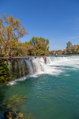 under a bright blue sky you can see the waterfall of Manavgat