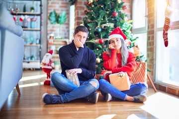 Young couple wearing santa claus hat sitting on the floor around christmas tree at home thinking looking tired and bored with depression problems with crossed arms.