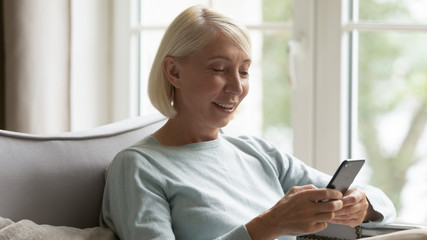 Happy mature woman sitting on cozy couch, using smartphone.