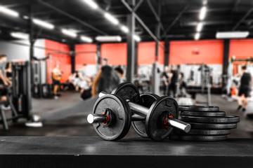 Keuken foto achterwand Fitness Dumbbell, barbell and workout in the gym. Copy space with blurred gym background.
