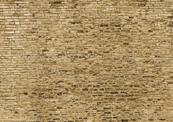 a sepia toned large rough textured brown wall made of old sandstone bricks
