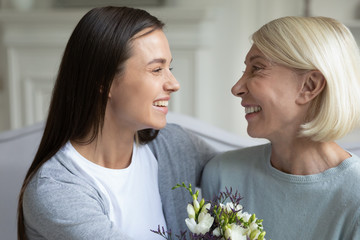 Millennial grown up daughter congratulating middle age mother with birthday.