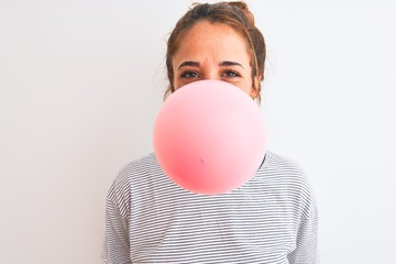Young redhead woman chewing gum and blowing hair bubble over white isolated background with a happy face standing and smiling with a confident smile showing teeth