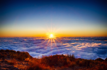 Fotorollo Sonnenuntergang Nature background with sunrise over clouds. It is on the top of Pico do Arieiro mountain, Madeira island, Portugal. The rising sun has a golden color.