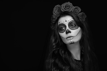 Portrait of a woman with sugar skull makeup over black background. Halloween costume and make-up. Black and white Portrait of Calavera Catrina