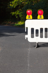 Partially Closed Road / Detail of street barrier with signal lamps at rural road (copy space)