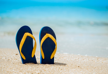 Flip flops on the white sand beach with blue sea background