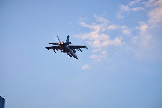 Australian Air Force fighter jet flying through Brisbane at sunset