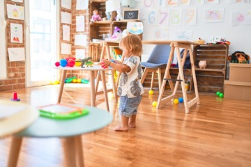 Adorable toddler playing around lots of toys at kindergarten