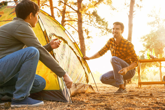 Friends putting up camping tent in forest