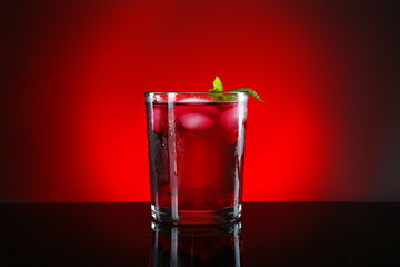 Glass of tasty cocktail on dark color background