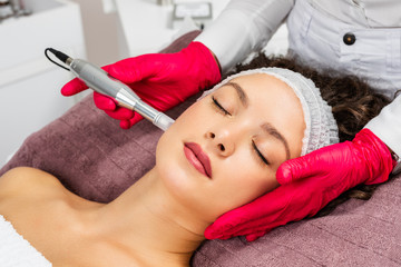 Beautiful woman receiving microneedling rejuvenation treatment. Mesotherapy.