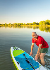 Senior adult with  inflatable stand up paddleboard