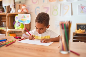 Beautiful african american toddler sitting drawing using paper and pencils on desk at kindergarten