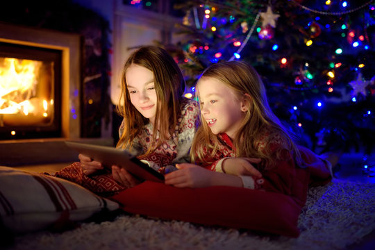 Two cute young sisters using a tablet pc at home by a fireplace in warm and cozy living room on Christmas eve.