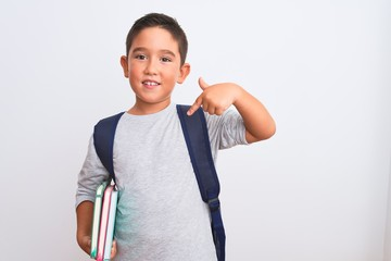 Beautiful student kid boy wearing backpack holding books over isolated white background with surprise face pointing finger to himself