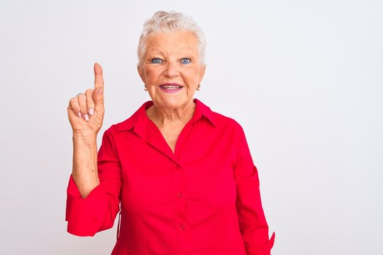 Senior grey-haired woman wearing red casual shirt standing over isolated white background showing and pointing up with finger number one while smiling confident and happy.
