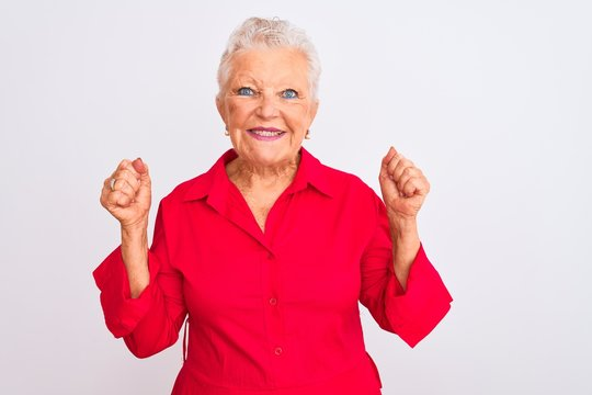 Senior grey-haired woman wearing red casual shirt standing over isolated white background excited for success with arms raised and eyes closed celebrating victory smiling. Winner concept.