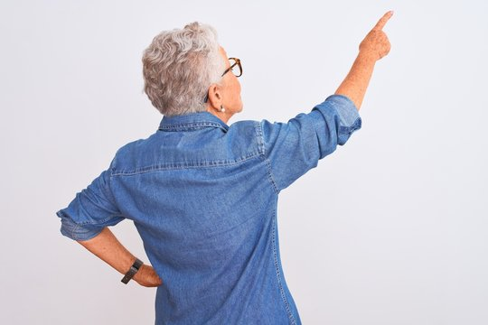 Senior grey-haired woman wearing denim shirt and glasses over isolated white background Posing backwards pointing ahead with finger hand