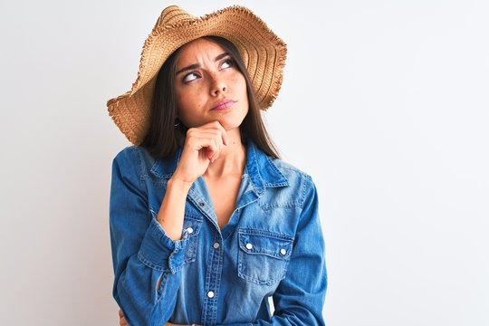 Young beautiful woman wearing denim shirt and hat standing over isolated white background with hand on chin thinking about question, pensive expression. Smiling with thoughtful face. Doubt concept.