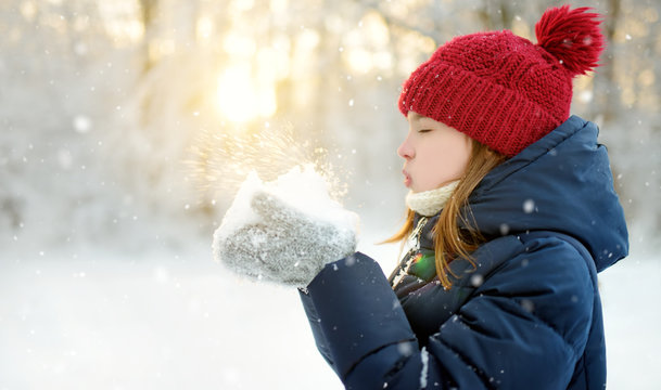 Adorable young girl having fun in beautiful winter park. Cute child playing in a snow. Winter activities for family with kids.