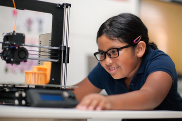 A happy young girl wearing glasses and watching a 3d printer finish the 3d model she created.