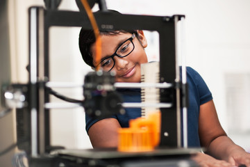 A smart little girl admiring her 3D printed model from behind the 3D printer.