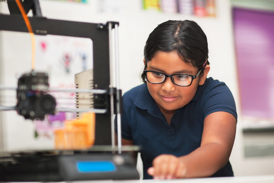 A female student in a modern classroom observing the printing process of a 3d model.