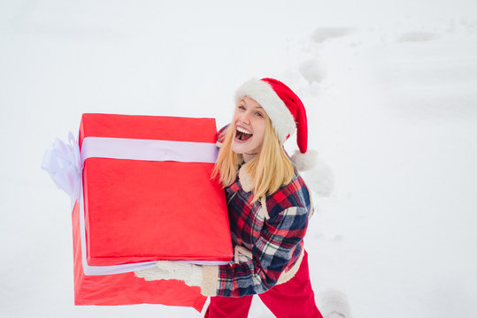 Promotion and bonuses. Merry Christmas and Happy Holidays. Christmas winter people. Give gift. Portrait of Santa woman with huge red gift looking at camera.