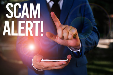 Text sign showing Scam Alert. Business photo showcasing fraudulently obtain money from victim by persuading him Man with opened hands stands in suite. Concept with copy space and man