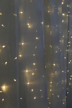 night led light wall garland on white tulle fabric backdrop, festive decoration, vertical stock photo image background