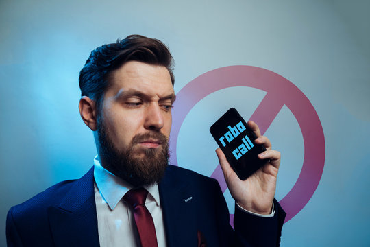 Man frowning receiving telemarketing robo call
