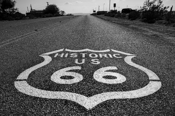 Horizontal greyscale shot of the 'Historic US 66' sign on the Route 66 street surrounded by trees
