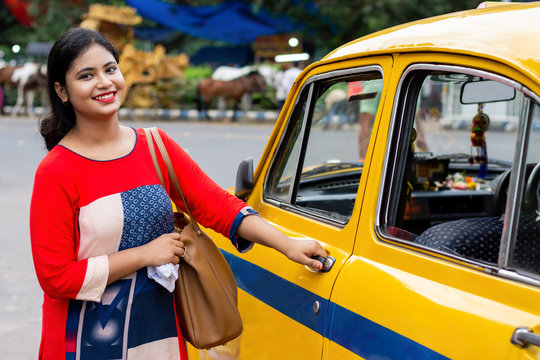Young Indian woman opening gate of old yellow taxi