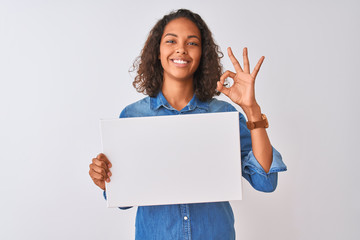 Young brazilian woman holding banner standing over isolated white background doing ok sign with fingers, excellent symbol