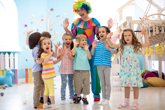 Clown and children group playing indoor . Holiday in a children's club. Games with animator