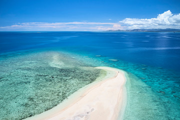 Person on remote island in Fiji overlooking blue coral reef