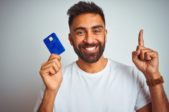 Young indian customer man holding credit card standing over isolated white background surprised with an idea or question pointing finger with happy face, number one