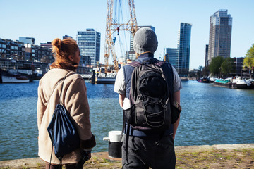 Foto auf Leinwand Rotterdam Young couple tourists looking and pointing to Rotterdam city harbour, future architecture concept, industrial lifestyle people