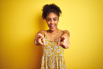 African american woman wearing casual floral dress standing over isolated yellow background pointing to you and the camera with fingers, smiling positive and cheerful